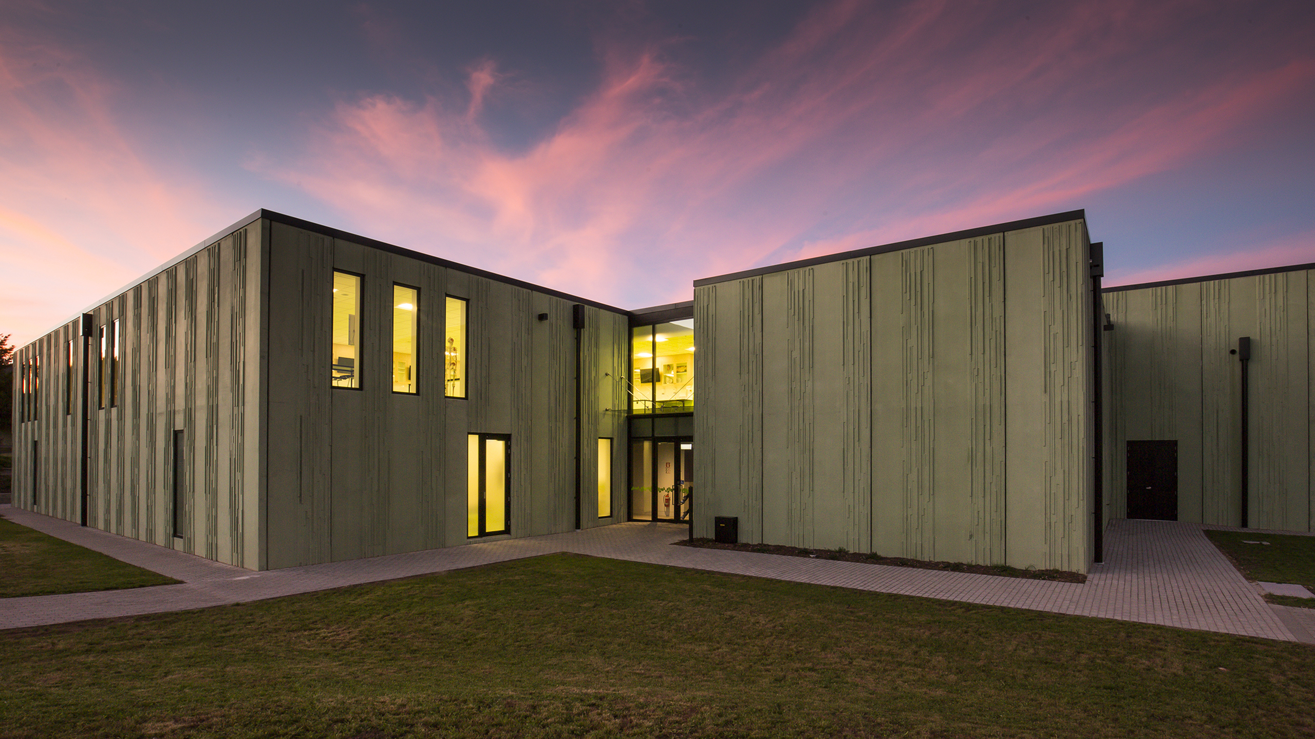 the sun sets behind the coloured concrete walls of Waiariki Nursing Building