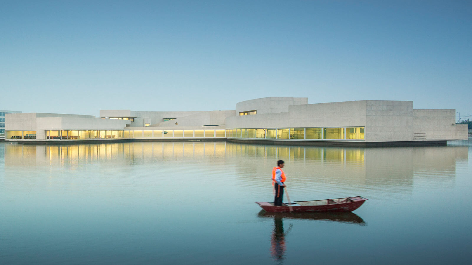 Man in a boat looks at a white concrete building.