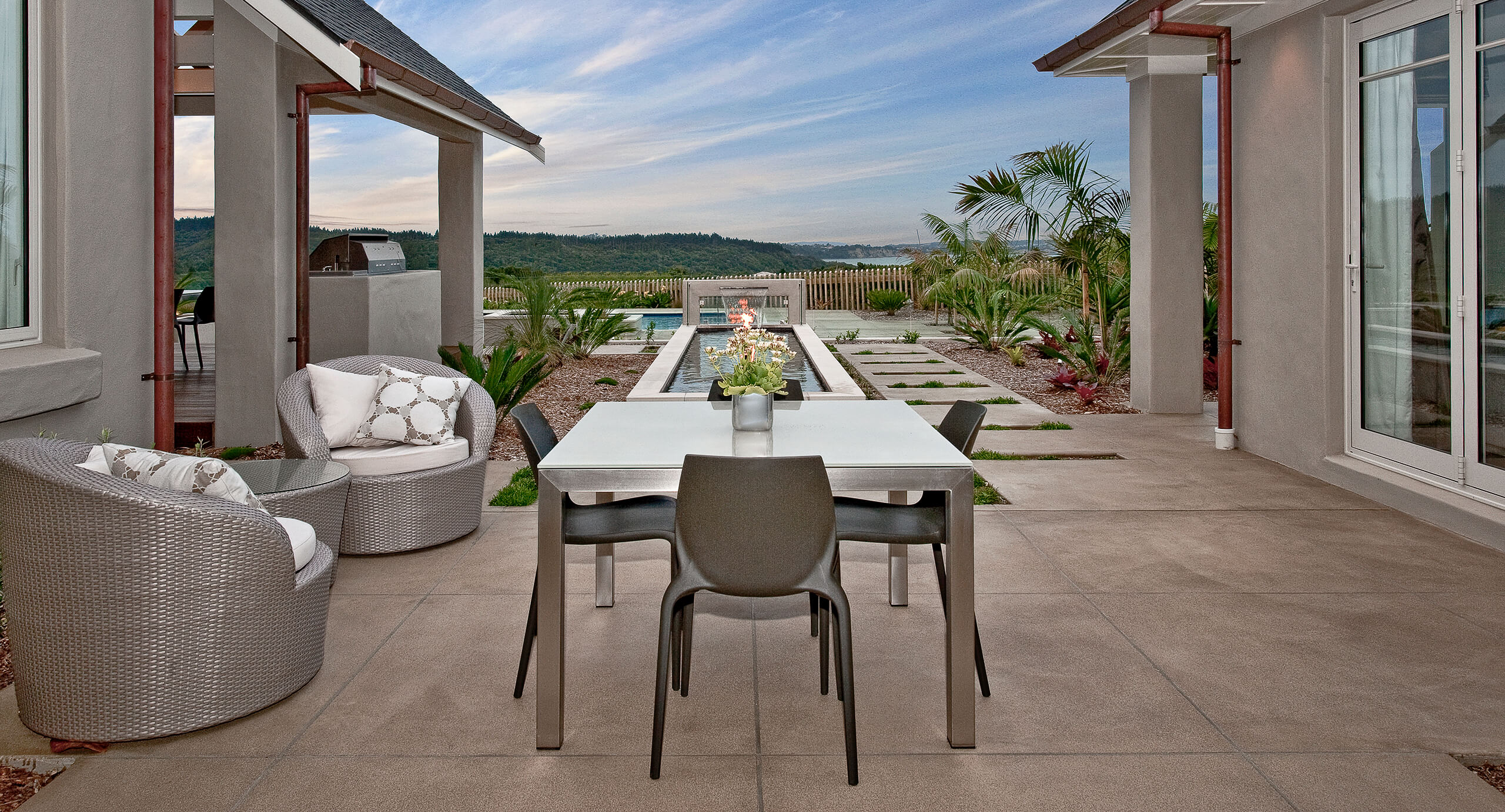 coloured concrete patio with dining table overlooking pool.