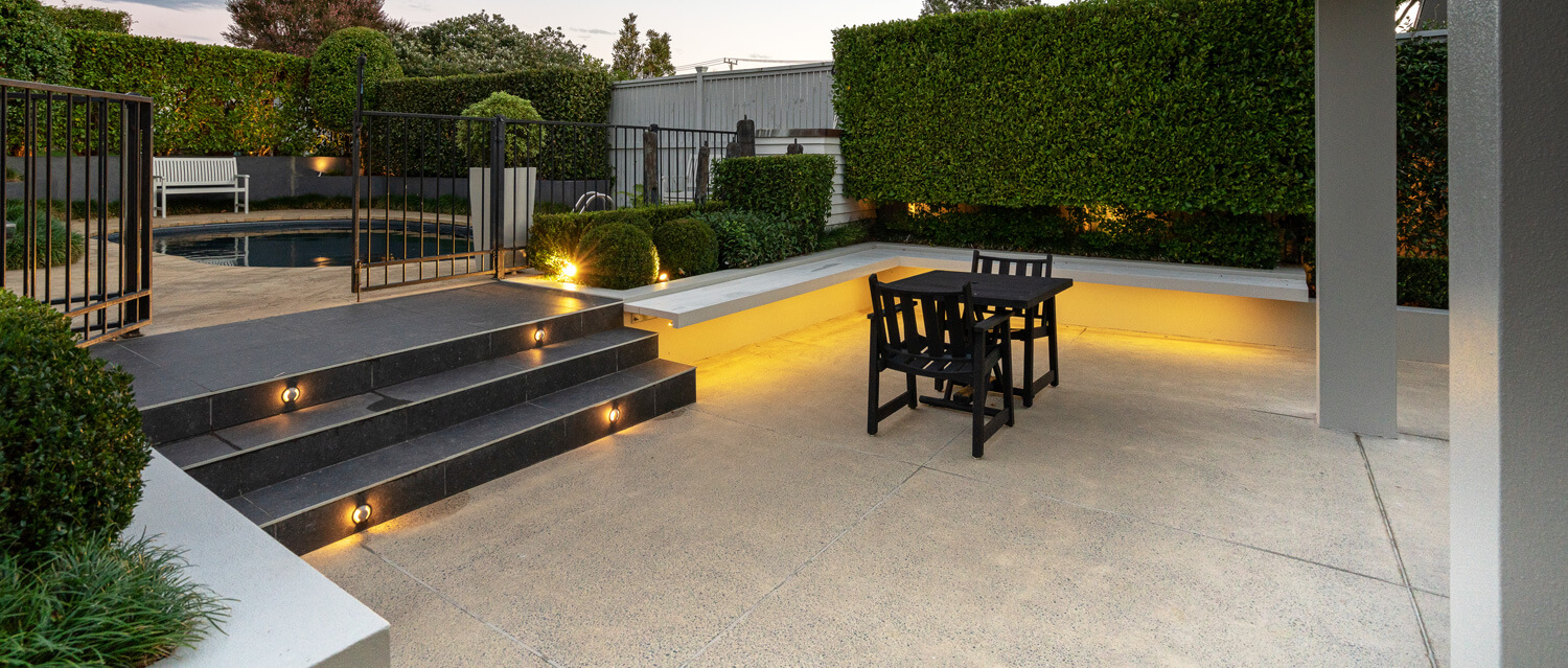 coloured concrete patio and pool surround with lights on stairs